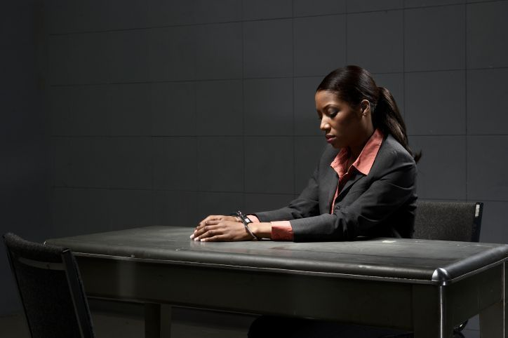 Young woman in handcuffs sitting at table